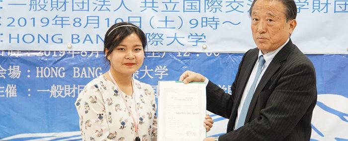 Ông Kikukawa Naganori - Đại diện Quỹ học bổng KYORITSU trao suất học bổng cho Nguyễn Thu Trinh - Sinh viên ngành Nhật Bản học HIU (Ảnh HIU)